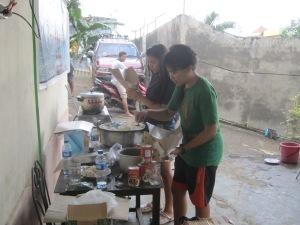 Caroline, helping prepare ready-to-eat food to distribute to refugees. | Caroline membantu menyiapkan makanan bungkus untuk dibagikan pada para pengungsi.