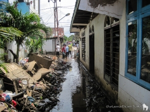 Waste washed to the alley by the flood is piled up to the side to make way for people to pass. | Sampah yang terbawa banjir untuk sementara ditumpuk di sisi lorong agar bisa dilalui.