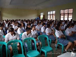 The hall was packed with students, and some teachers joined in as well. | Aula dipenuhi siswa, dan beberapa guru juga turut mendengarkan.
